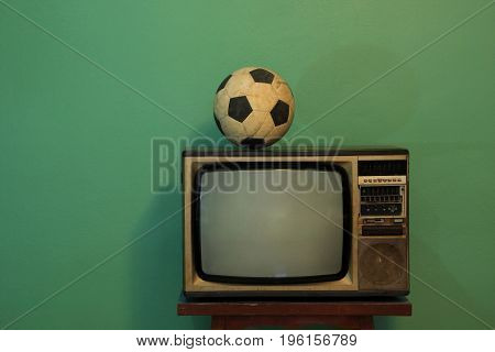 An old soccer ball on a retro TV with retro green paint wall.