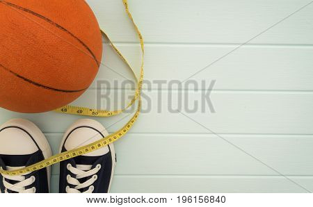 Sport and Health concept image - Basketball Measuring Tape Sneakers flat lay on wooden background with copy space.
