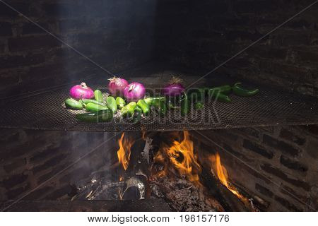 Traditional brick fire barbecue with red onions and jalapeno peppers on grill over fire as sunlight beams down through chimney