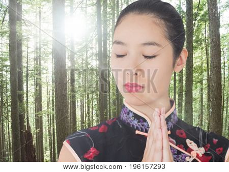Digital composite of Close up of geisha with hands together in forest with flare