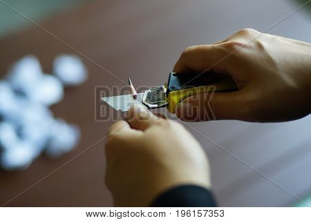 Asian woman's hands sharpening pencil with blurred background.