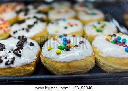 Display Of White Glazed Donuts On Tray Topped With Candy Coated Chocolate Peices And Cookies