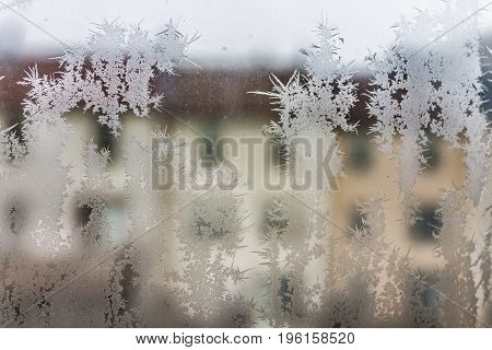 Ice crystals on window with view of town houses during winter