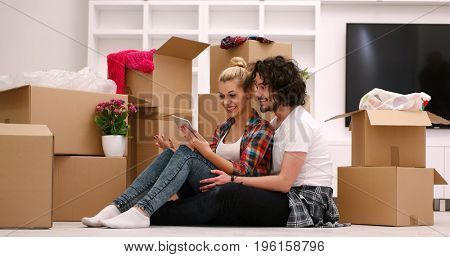 Relaxing in new house. Cheerful young couple sitting on the floor while cardboard boxes laying all around them