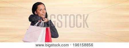 Digital composite of Shopper over shoulder with bags against blurry cream background