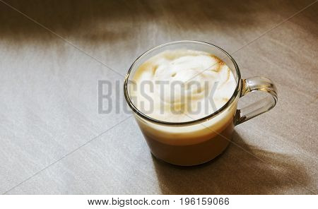 Glass mug with foamy cappuccino on a rough marbled floor . Interior shot