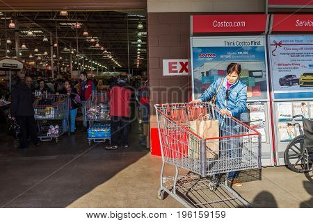 Fairfax, Usa - December 3, 2016: People With Shopping Carts Filled With Groceries Walking Out Of Cos