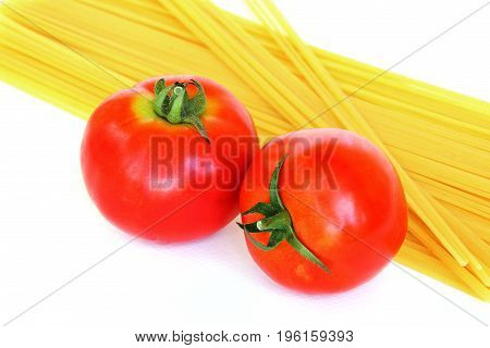 Fresh tomatoes with raw pasta as background.