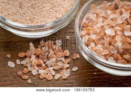 fine and coarse crystals of pink  Himalayan salt in glass bowls on rustic wood
