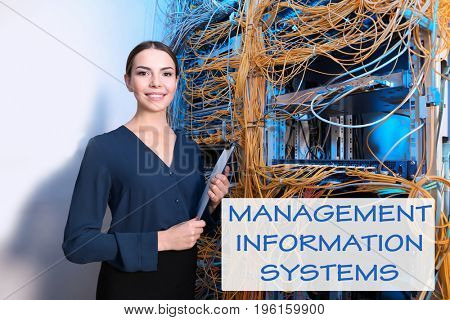 Concept of management information systems. Young engineer with clipboard in server room