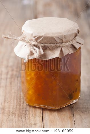 Cloudberry jam in a glass jar an old wooden table