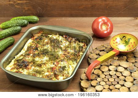 VegetVegetables baked with tomatoes and cucumbers in a rustic mannerables baked with tomatoes and cucumbers