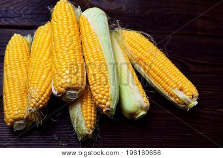 Pile of fresh corn cobs on a brown wooden background