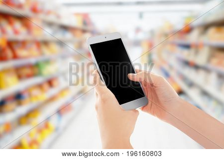 Woman holding smartphone and blurred shelves with different products on background. Internet shopping concept