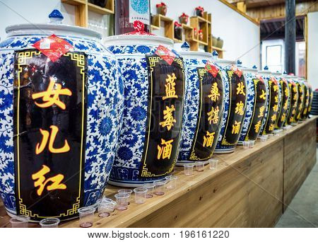 Suzhou, China - Nov 5, 2016: At the historic Zhouzhuang Water Town. A wine store selling a variety of traditional Chinese wines in ornate ceramic urns. Taster cups left on bench by tourists after tasting session.