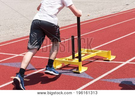 A high school boy pushes a yellow sled on a red track at track and field practice