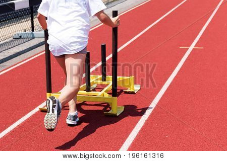 A high school girl pushes a yellow sled on a red track at track and field practice for leg strength