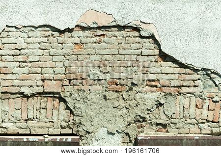 Damaged plaster - mortar on old house exterior brick wall.