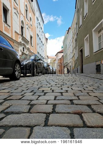 Street lined with cobblestone with many parked cars on the side