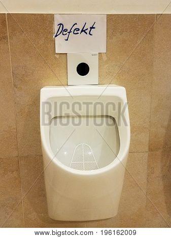 German language hand written sign over a broken urinal