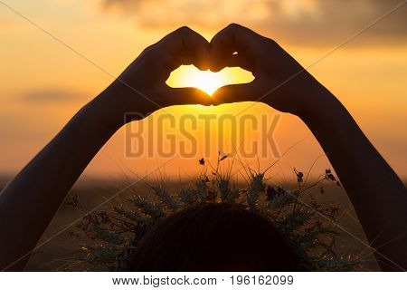 Silhouette of girl hands making heart symbol at sunset, outdoor