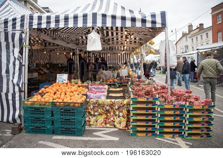 SUDBURYUK - MARCH 18 2017 : Shoppers look around a fruit and vegetable stall in a town market