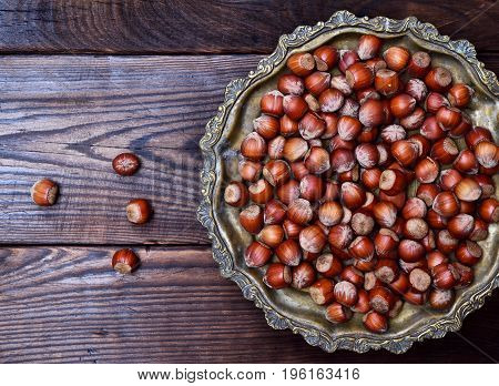 Hazelnut nut in shell on an iron copper plate top view