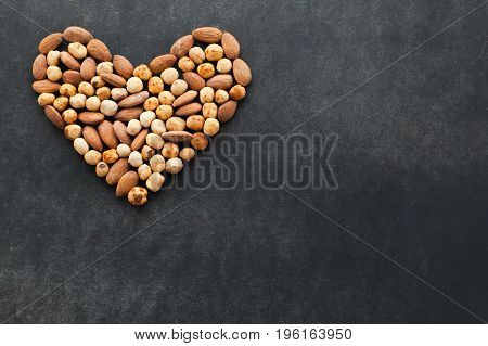 Assortment of nuts on black background in heart shape with free space for text. Healthy snack for keeping you in good shape.