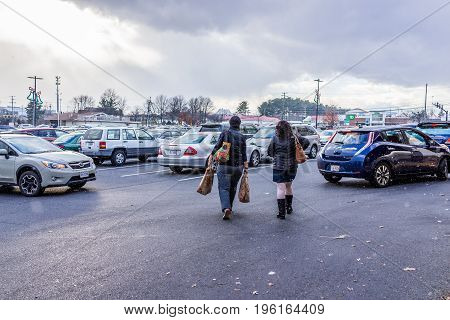 Fairfax, Usa - December 30, 2016: Women Walking During Snow Fall With Trader Joes Bags To Car In Par