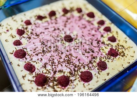 Raspberry Cheesecake In Blue Glass Pan Decorated With Chocolate Shavings