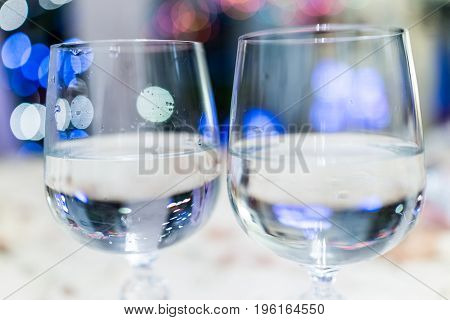 Macro Closeup Of Two Crystal Wine Glasses With Blue Bokeh Lights And Clear Water