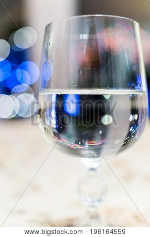 Macro Closeup Of One Crystal Wine Glass With Blue Bokeh Lights And Clear Water
