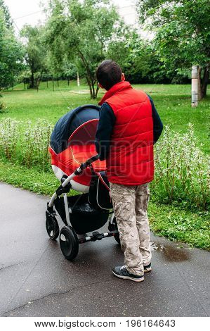 back of a young man walking with a stroller