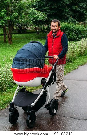 young man walking with a stroller in the Park
