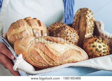 Woman Holding Different Kinds Of Fresh Bread.