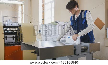 Printing process - worker inserts paper sheets in industrial press, wide angle