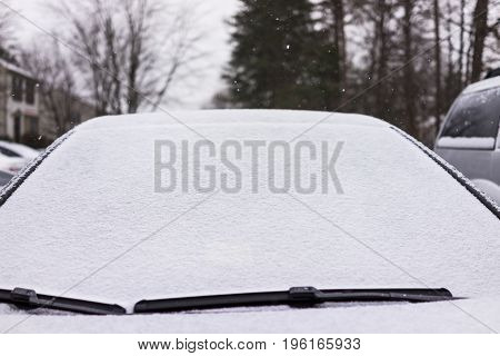 Snow Covered Windshield On Car With Wipers