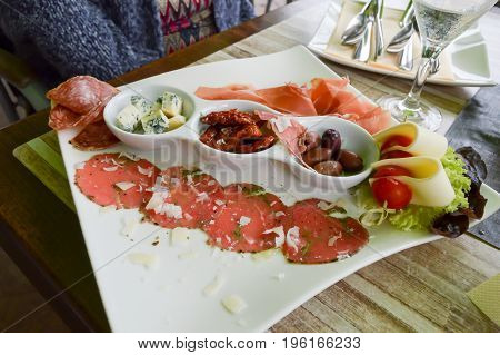 Plate of carpaccio of beef salami smoked ham and cheeses
