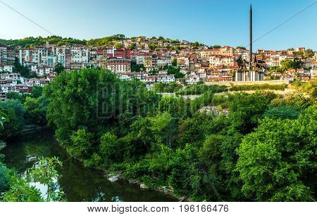 VELIKO TARNOVO BULGARIA - JULY 06 2012: View of the part of the ancient Bulgarian capital Veliko Tarnovo on the Yantra river and the monument to the kings of the Asen dynasty.