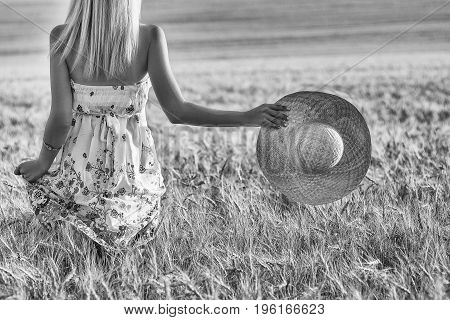 Happy young woman blonde in a wheat field with a straw hat in hand. black and white photo