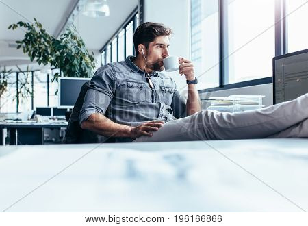 Young man drinking coffee during break in office. Businessman listening music with cup of coffee.