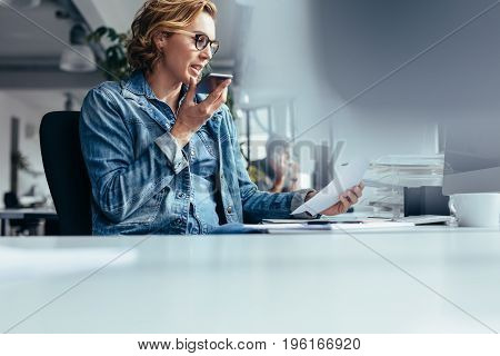 Young businesswoman talking on speaker phone with document. Young woman sitting in office with smart phone and looking at a paper.