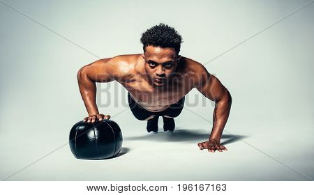 Horizontal shot of young fit man doing push up on medicine ball. Fitness male exercising with a medicine ball on grey background.