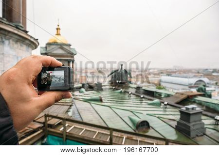 Tourist shoots video on action camera roof of St. Isaac's Cathedral in St. Petersburg, selective focus on hand with action camera