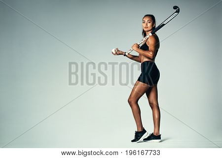 Female Hockey Player Over Grey Background