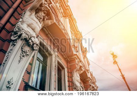 Facade of old building in St. Petersburg with statues of titans in sunshine, toned