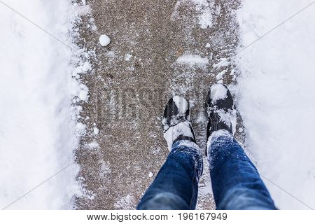 Sidewalk cleaned from winter snow with person's feet