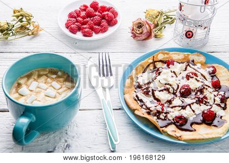 Homemade pancakes or Russian pancakes with chocolate sauce, whipped cream and raspberries on a plate on a white wooden background. Top view.