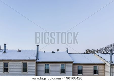 Row Of Townhouses During Winter With Snow Covering Roof