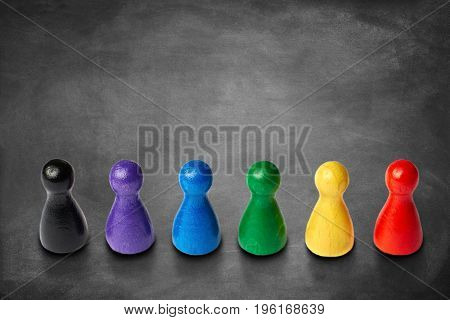 Colorful game figures standing in a line on a chalkboard background. With a lot copyspace